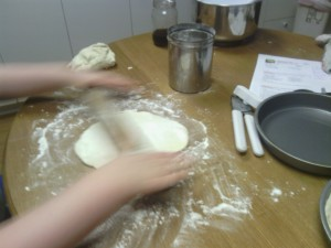 Rolling out the dough to fit our round pans!